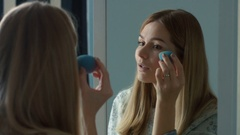 Portrait Of Blonde Woman applying make-up Stock Footage