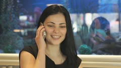Attractive model talking on a smartphone indoors Stock Footage