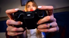 Girl holding a game joystick and clicks on buttons Stock Footage