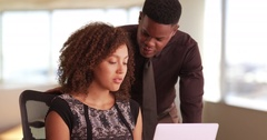 Two black millennials working in a highrise office Stock Footage