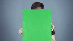 Curious Young man in black shirt holding green key sheet poster gray background Stock Footage