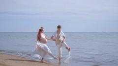 Love couple having fun on sea beach. Pregnant couple splashing water Stock Footage