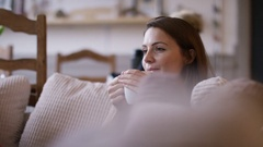 4K Attractive woman at home relaxing with a hot drink and tv Stock Footage