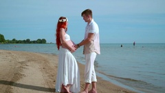 Pregnant couple beach. Man holding pregnant belly in hands. Expecting parents Stock Footage