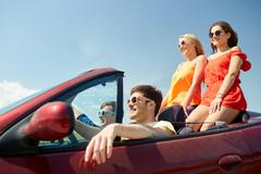 Happy friends driving in cabriolet car Kuvituskuvat