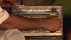 Close-up of hand trying to adjust signal of an old radio in an Indian village. Stock Footage
