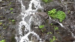 Small waterfall on steep rocky mountain Stock Footage