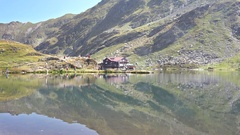 Alpine wooden cottage on shore of glacial lake on top of mountain Stock Footage
