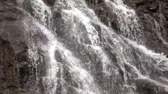 Multiple streams of waterfall on rocky mountain steep wall Stock Footage