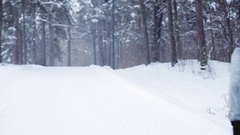 Man running on snow covered winter road in forest Arkistovideo