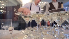 Two waiters fill champagne pyramid of wineglasses on restaurant Stock Footage