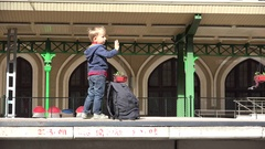 Lovely blond boy with backpack waving hand in train station, wait, ready to go Stock Footage