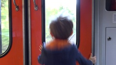 Happy child looking on train window and jumping, long expected travel Stock Footage