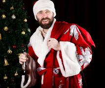 Bad brutal Santa Claus carries a bag, smiling spitefully and drinking brandy Stock Photos