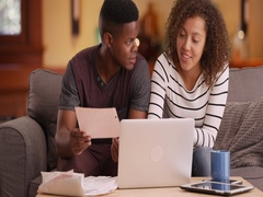 Millennial couple plans their retirement on their laptop Stock Footage