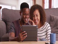 Authentic millennial black couple sits on floor watching a video on their tablet Stock Footage