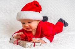Funny Christmas baby in Santa Claus costume lying on white blanket Stock Photos