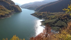 Sun shinning in calm glittering lake, autumn mountains Stock Footage