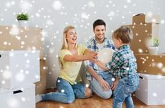 Happy family moving to new home and playing ball Stock Photos