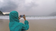 Woman taking picture with smart phone at Nai harn beach Stock Footage