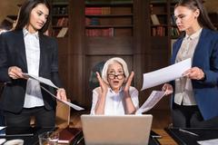 Exhausted boss and her female colleagues posing in an office Stock Photos