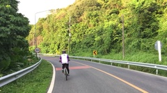 Healthy thai woman cycling down road bicycle outdoors fitness steadicam shot Stock Footage