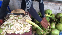 Street coconut seller chopping young coconut from a bunch with his hatchet Stock Footage