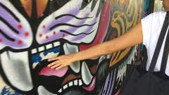 Young Woman Walks Along Colorful Mural Wall And Touching Graffiti art with her Stock Footage