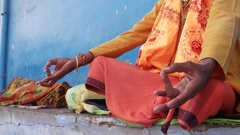 Tilt up to a Sadhu baba, Indian holy man, in between prayer looking straight at  Stock Footage