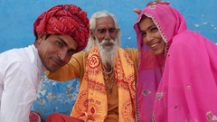 Indian holy man, Sadhu, hands raised and blessing a couple with folded hands in  Stock Footage