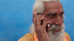 Closeup of an excited Hindu holy man communicating on a touch screen phone  Stock Footage