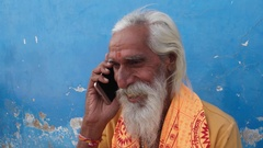 Handheld closeup of a Hindu Sadhu smiling while attending a call mobile phone Stock Footage