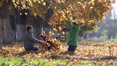 Happy family fighting with autumn leaves, golden nature, playful lifestyle   Stock Footage
