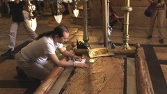 A man kisses the anointing stone inside the church of the holy sepulchre Stock Footage