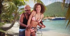African American couple ride their beach cruiser along the shore  Stock Footage
