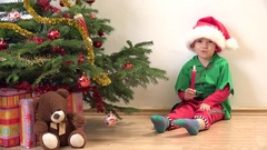Funny child with elf costume and lightning candle close Christmas tree Stock Footage