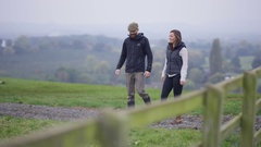 4K Farming couple walking in the field & checking on herd of cattle Stock Footage