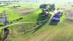 Flying above houses in green fields Stock Footage