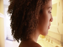 Close-up of black millennial girl with curly hair in her bathroom Stock Footage