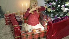 Little girl playing with a red gum at the Christmas gifts. Stock Footage