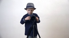 Portrait of little fashionable child arranging video camera, funny film director Stock Footage