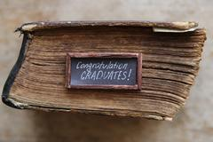 Congratulations graduates text and vintage book on table Stock Photos