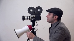 Portrait of man with video camera , director talking on megaphone Stock Footage