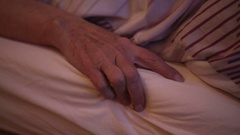 Closeup of old woman's hand lying in bed Arkistovideo