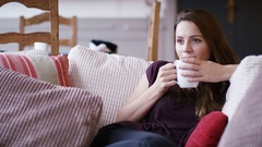 4K Young woman on her couch watching tv reacts in surprise Stock Footage