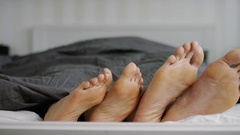 4K Happy feet of a couple doing a silly dance in bed Stock Footage