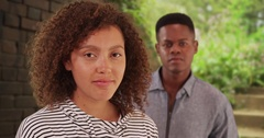 Young black man and woman pose for a picture near a brick wall Stock Footage