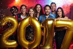 Group of joyful friends standing in confetti rain and holding 2017 shaped balloo Kuvituskuvat
