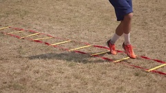 American football player does speed and agility ladder drills close-up Stock Footage