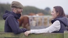 4K Farming couple talking in the field with cattle grazing in background Stock Footage